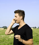 Male talking on phone outside. A young male talking on phone outside Stock Photos