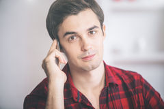 Male talking on phone. Portrait of attractive young male in casual red shirt talking on cellular phone Royalty Free Stock Image