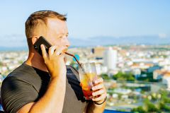 Male talking on the phone and working on a laptop in a rooftop cafe with a panoramic view. man drinking a cocktail and royalty free stock image