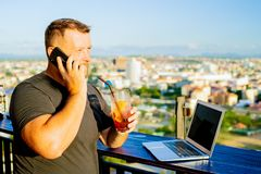 Male talking on the phone and working on a laptop in a rooftop cafe with a panoramic view. man drinking a cocktail and stock photos