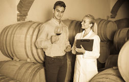 Male talking with technician. Male owner of winery talking with technician in cellar Stock Image