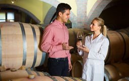 Male talking with technician. Male owner of winery having conversation with employee technician in cellar Stock Photo