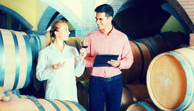 Male talking with technician. Male owner of winery 40s having conversation with technician in cellar Stock Image