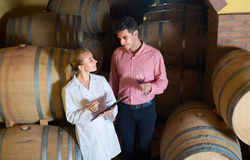 Male talking with technician. Portrait of male owner of winery having conversation with technician in cellar Royalty Free Stock Photo