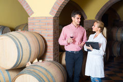Male talking with technician. Male sommelier having conversation with technician in cellar Royalty Free Stock Photo