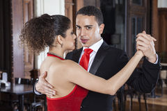 Male Tango Dancer Performing Gentle Embrace With Partner. Portrait of male tango dancer performing gentle embrace with partner in restaurant Royalty Free Stock Images