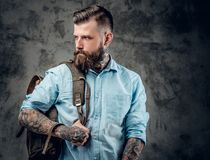 Male with tattooes on his arms and neck. Portrait of stylich beard male with tattooes on his arms and neck with backpack on his shoulder Stock Photo