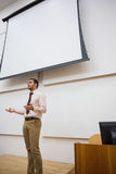Male teacher against projection screen in lecture hall. Elegant male teacher standing against projection screen in the lecture hall Stock Photography