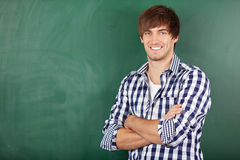 Male Teacher With Arms Crossed Standing Against Chalkboard. Portrait of handsome young male teacher with arms crossed standing against chalkboard Royalty Free Stock Photography