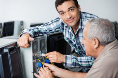 Male Teacher Assisting Senior Man In Fixing Computer. Portrait of male teacher assisting senior men in fixing computer at classroom Stock Image