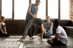 Male teacher assisting woman doing yoga bridge exercise on mat. Male teacher assisting young women doing yoga exercise on mat, instructor helping flexible girl royalty free stock image
