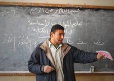 Male teacher in classroom explaining on blackboard Stock Photography