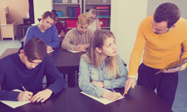 Male teacher clearing up complicated issue to pupil during exam. Positive english male teacher clearing up complicated issue to pupil during exam in class Royalty Free Stock Images