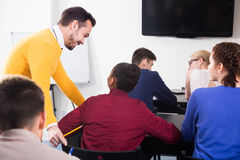 Male teacher clearing up complicated issue to pupil during exam. Positive italian male teacher clearing up complicated issue to pupil during exam in class Royalty Free Stock Image