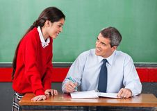 Male Teacher Discussing With Schoolgirl At Desk. Mature male teacher discussing with schoolgirl at desk in classroom Royalty Free Stock Photo
