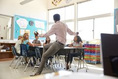 Male teacher with elementary school kids in school class stock image