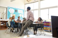 Male teacher with elementary school kids in school class royalty free stock photo