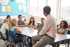 Male teacher with elementary school kids in class discussion stock photography