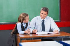 Male Teacher Explaining Lesson To Schoolgirl. Mature male teacher explaining lesson to little schoolgirl at desk in classroom Royalty Free Stock Photos