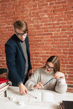 Male teacher explaining mistakes to student. Young coach teaching dummy student, new material studying, free space. Education, private lessons, hard stock photos