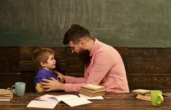 Male teacher explaining something to the boy. Side view bearded man in glasses and blond child in front of green board. Male teacher explaining something to the royalty free stock photos