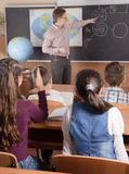 Male teacher in front of elementary age pupils. Male teacher in front of elementary age schoolchildren Stock Image