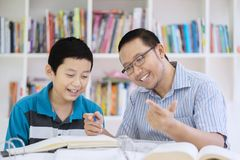Male teacher guides his student to count. Picture of male teacher guides his student to count while sitting in the library Royalty Free Stock Photo