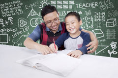 Male teacher guides his student to learn. Young male teacher guides his student to learning while sitting in the classroom with scribbles on the chalkboard Stock Image
