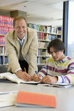 Male teacher helping male student to study in library, smiling, portrait Stock Photography
