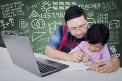 Male teacher helps his student to write Stock Photo
