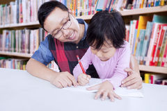 Male teacher helps student to write Royalty Free Stock Images