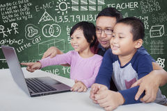 Male teacher and his students using laptop Royalty Free Stock Photography