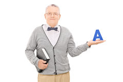Male teacher holding book and the letter a Stock Images
