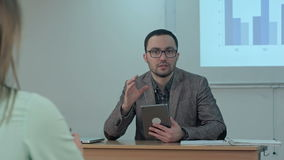 Male teacher holding digital tablet sitting in front of students and talk to a camera. Professional shot in 4K resolution. 075. You can use it e.g. in your stock footage