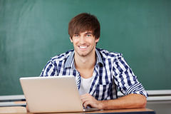 Male Teacher With Laptop Sitting At Desk Against Chalkboard Stock Images