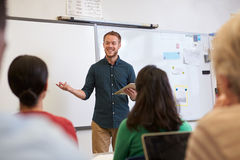 Male teacher listening to students at adult education class Royalty Free Stock Images
