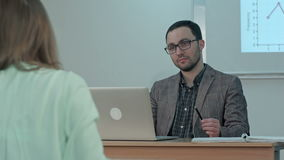 Male teacher listening to students at adult education class stock footage