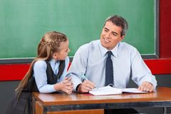 Male Teacher Looking At Schoolgirl In Classroom. Mature male teacher looking at schoolgirl against chalkboard in classroom Royalty Free Stock Photos