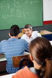 Male Teacher Looking At Student. Mature male teacher looking at student while crouching at desk in classroom Royalty Free Stock Images