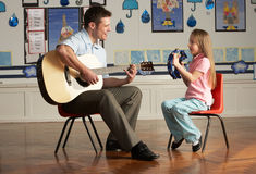 Male Teacher Playing Guitar With Pupil In Classroo. M Having Fun Royalty Free Stock Photography