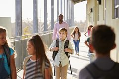 Male teacher and pupils walk on elementary school campus royalty free stock images