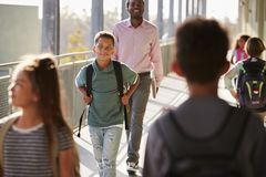 Male teacher and pupils walking on busy school campus royalty free stock photos