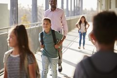 Male teacher and pupils walking in school campus stock images
