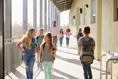 Male teacher and pupils walking on school campus royalty free stock photography