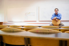 Male teacher sitting on chair in lecture hall. Portrait of a male teacher sitting on chair in the lecture hall Stock Photos