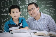 Male teacher sitting with his student in classroom. Male teacher smiling at the camera while sitting with his student in the classroom Stock Images