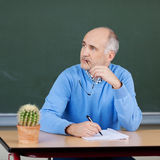 Male teacher sitting thinking. At his desk holding his glasses in his hand and staring off to the side in contemplation Royalty Free Stock Photography