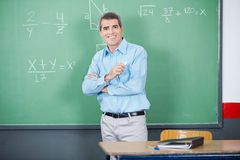 Male Teacher Standing Arms Crossed Against Board Stock Photography