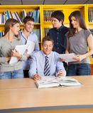 Male Teacher And Students In Library Royalty Free Stock Images