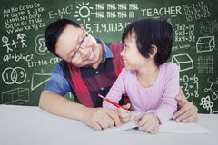 Male teacher teach little girl in class. Portrait of young male teacher smiling at a little girl while teaching her in the classroom Stock Image